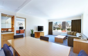 Sydney hotel suite with expansive lounge area overlooking the city, at Holiday Inn Potts Point.